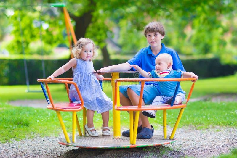 Trois enfants adorables sur une oscillation photographie stock