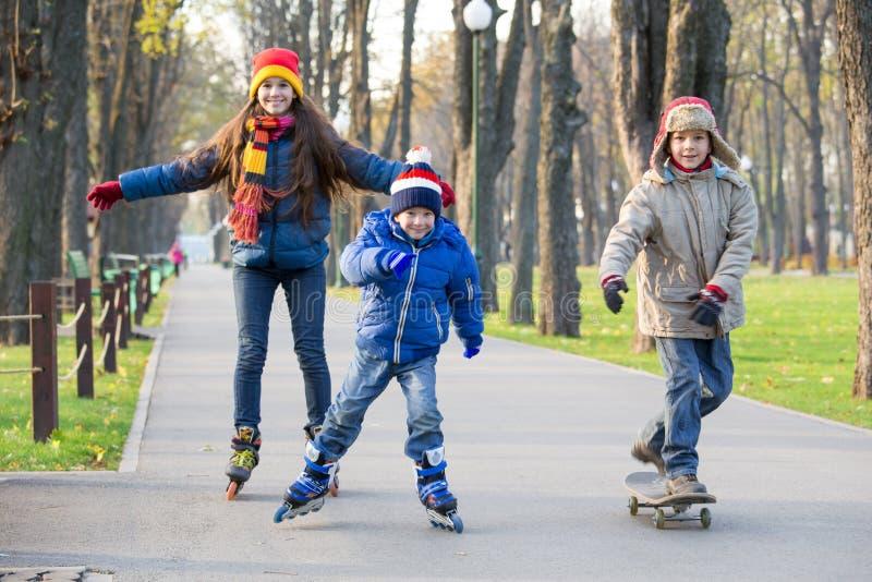 Trois enfants apprenant à monter en parc d'automne fait du roller dessus photo stock