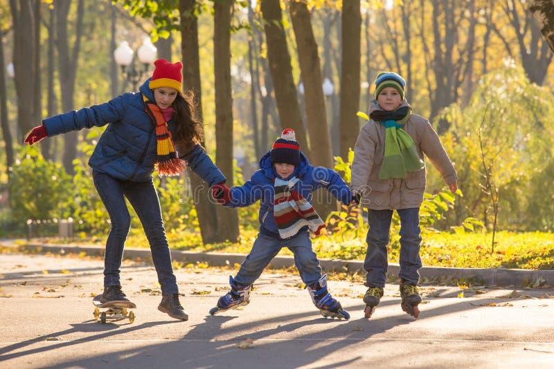Trois enfants apprenant à monter en parc d'automne fait du roller dessus et s photographie stock