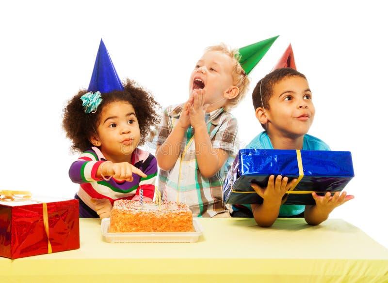 Trois enfants avec le gâteau d'anniversaire et les peresents photographie stock libre de droits