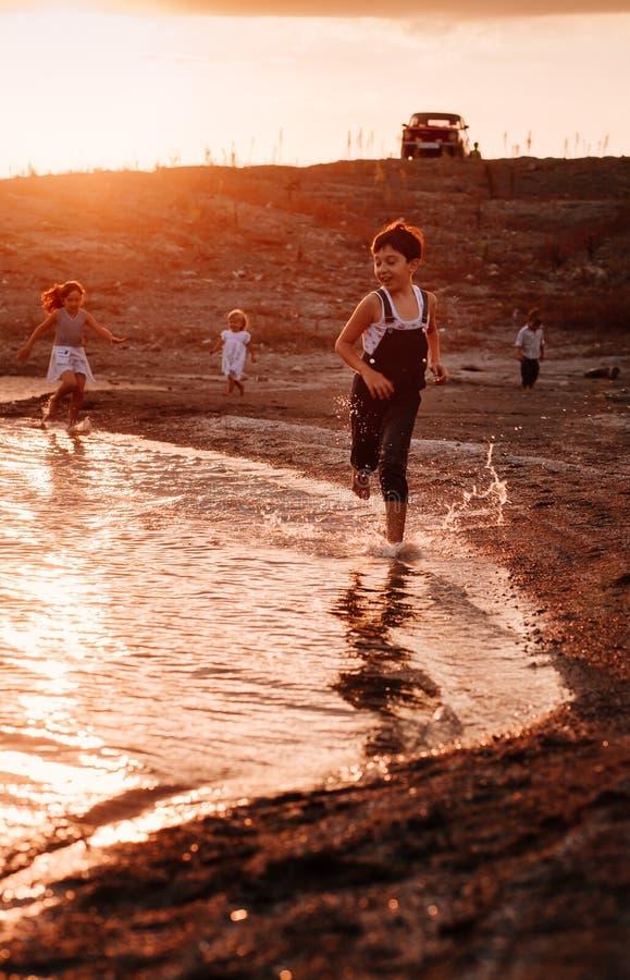 Trois enfants courant le long de la plage image stock