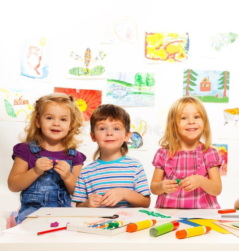 Trois enfants créatifs sur la leçon photographie stock libre de droits