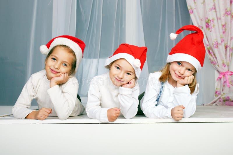 Trois enfants dans des chapeaux de Noël photos stock