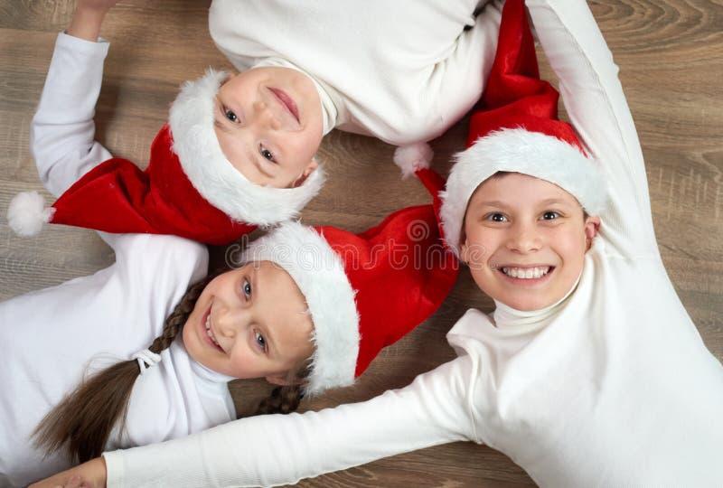 Trois enfants dans des chapeaux de Santa se trouvant sur le fond en bois, ayant l'amusement et les émotions heureuses, concept de photos stock