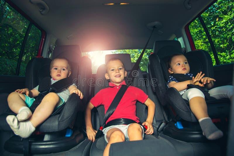 Trois enfants dans le siège de sécurité de voiture photographie stock
