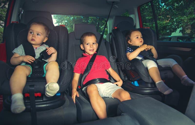 Trois enfants dans le siège de sécurité de voiture photos stock