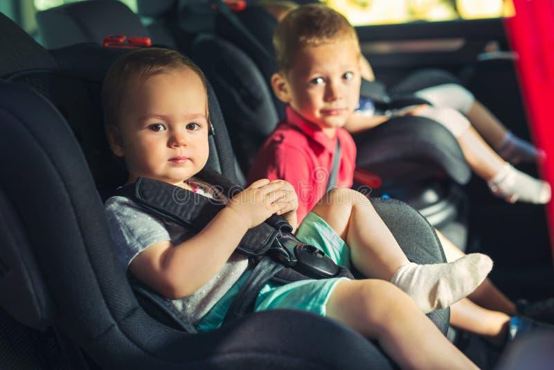 Trois enfants dans le siège de sécurité de voiture image stock