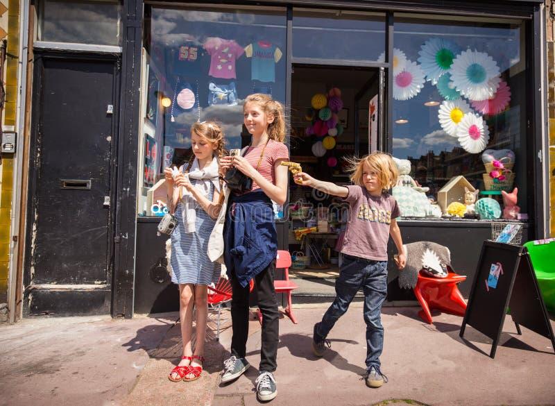 Trois enfants en dehors d'un jouet de Londres font des emplettes, un petit garçon dessine une arme à feu de jouet photos libres de droits