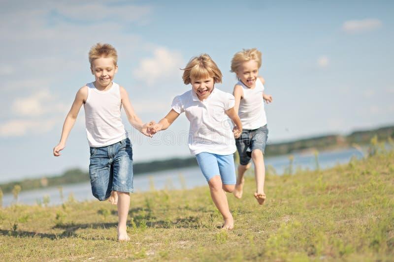 Trois enfants exécutent sur un fond coloré photographie stock libre de droits