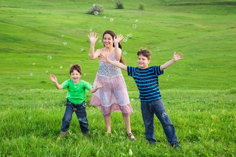 Trois enfants heureux attrapent les bulles de savon sur la pelouse photographie stock libre de droits