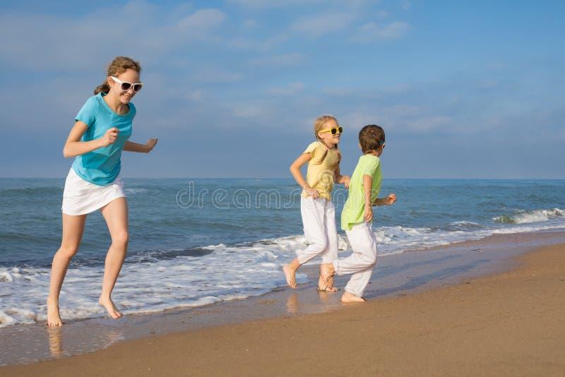 Trois enfants heureux courant sur la plage au temps de jour images stock