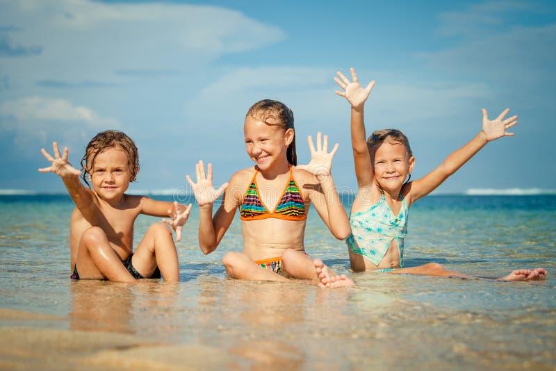 Trois enfants heureux jouant sur la plage photos stock