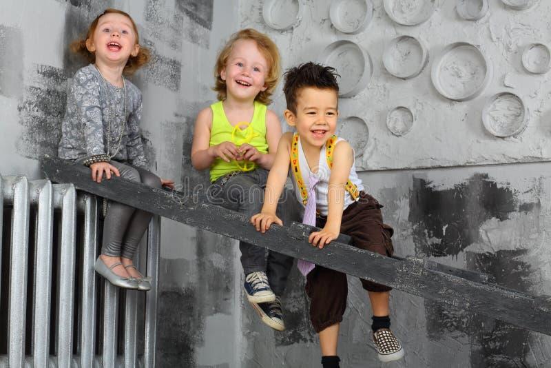 Trois enfants heureux s'asseyant sur les escaliers photos stock