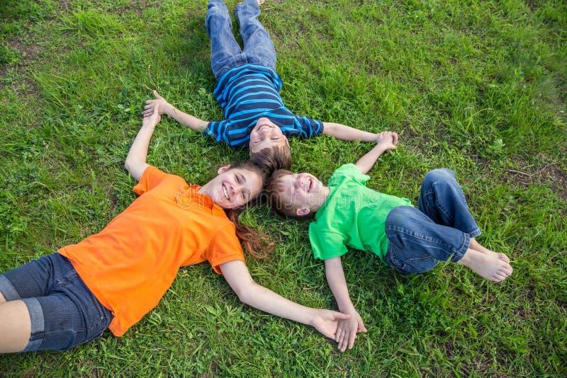 Trois enfants heureux se couchant sur l'herbe verte photo libre de droits