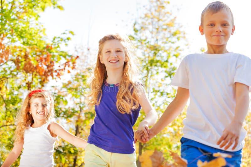 Trois enfants heureux tiennent des mains dans la vue de plan rapproché de parc photos libres de droits