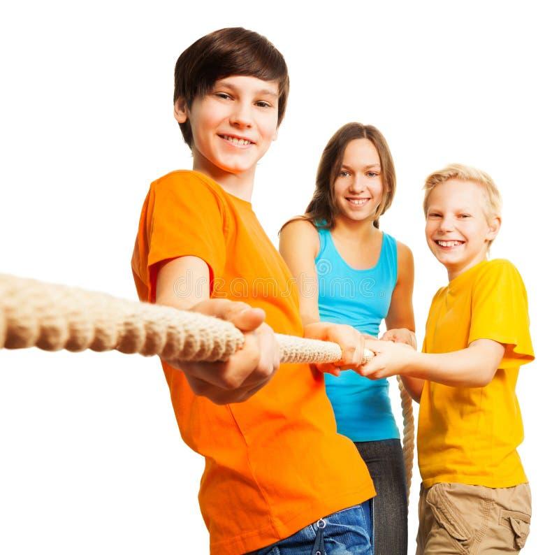 Trois enfants heureux tirent la corde photo libre de droits
