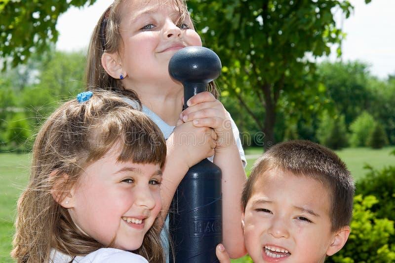 Trois enfants jouant au stationnement photographie stock libre de droits