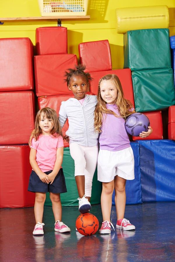Trois enfants jouant le football dans le gymnase images stock