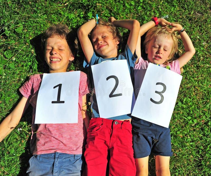 Trois enfants luying sur l'herbe images libres de droits