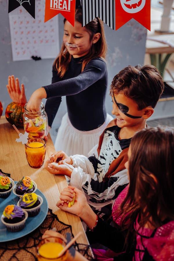 Trois enfants mangeant des petits gâteaux tout en ayant la partie de Halloween dans le jardin d'enfants photographie stock libre de droits