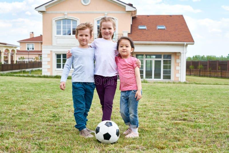 Trois enfants posant dehors image stock