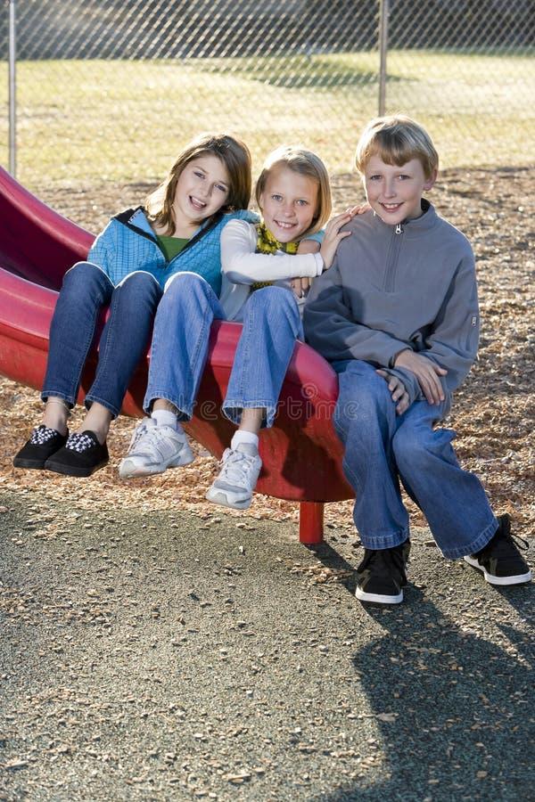 Trois enfants s'asseyant sur la glissière images libres de droits