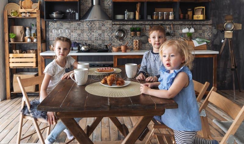 Trois enfants s'asseyent à la table et boivent du thé dans la cuisine avec les pâtisseries fraîches image libre de droits