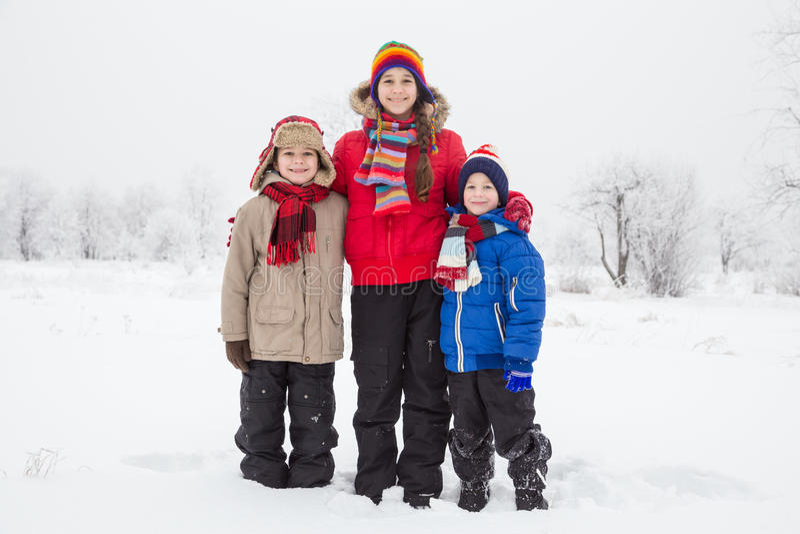 Trois enfants se tenant ensemble sur la neige d'hiver photo libre de droits