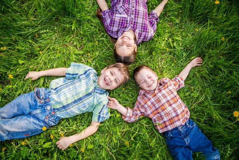 Trois enfants sur l'herbe avec des pissenlits photos stock