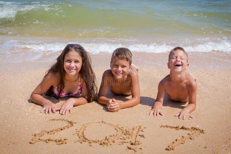 Trois enfants sur la plage avec le signe de la nouvelle année 2017 photographie stock libre de droits