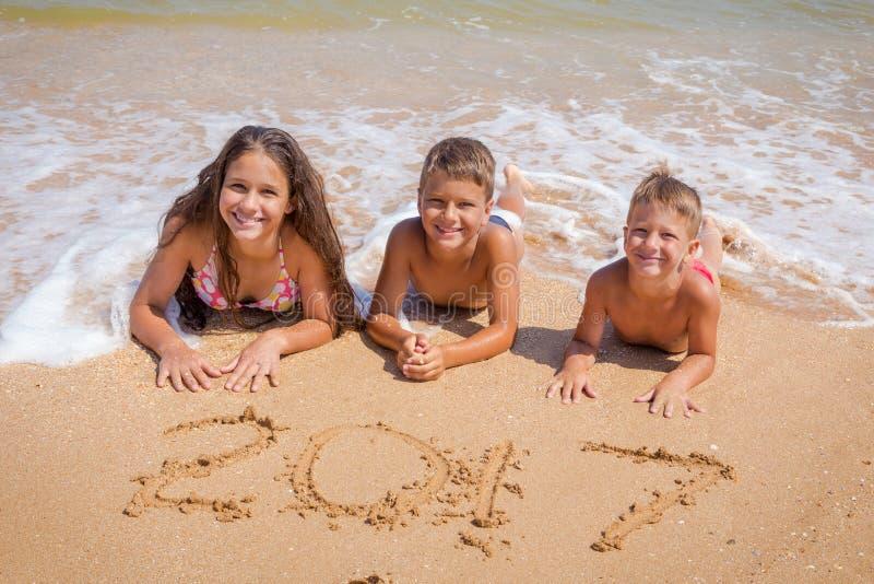 Trois enfants sur la plage avec le signe de la nouvelle année 2017 images libres de droits