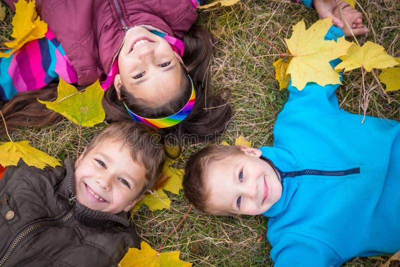Trois enfants sur les feuilles jaunes photos stock