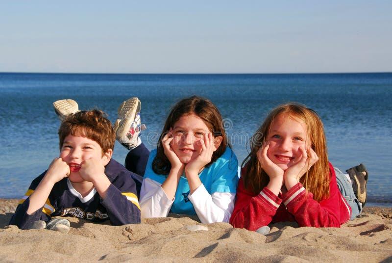 Trois enfants sur une plage photos stock