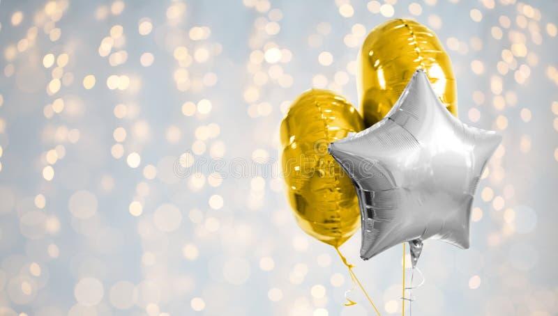 Or trois et ballons argentés d'hélium sur le blanc images stock