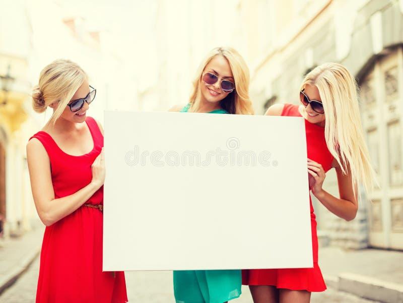 Trois femmes blondes heureuses avec le conseil blanc vide image stock