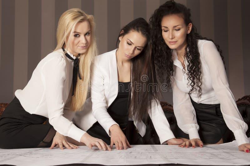Trois femmes d'affaires au bureau fonctionnant avec l'ordinateur portable photographie stock