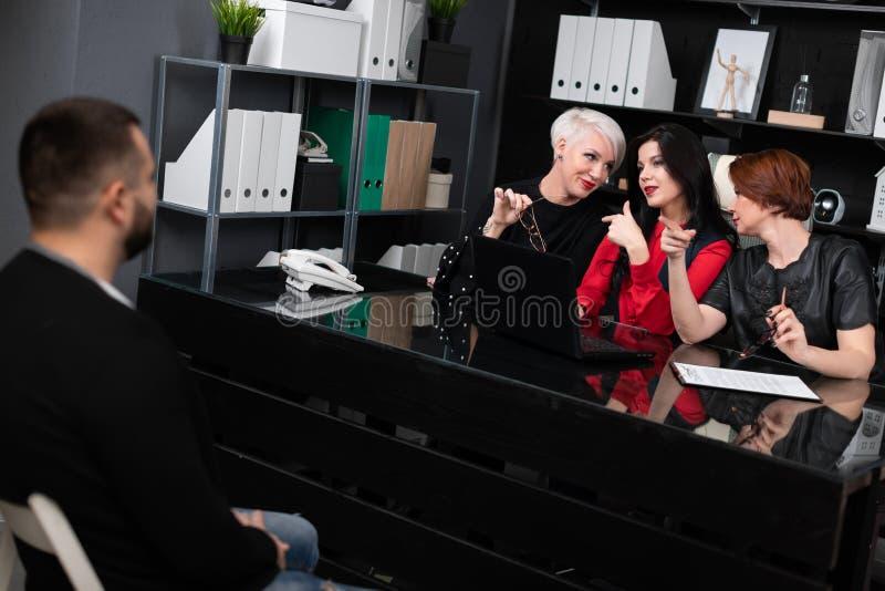 Trois femmes d'affaires regardent l'homme dans le local commercial appraisingly images libres de droits