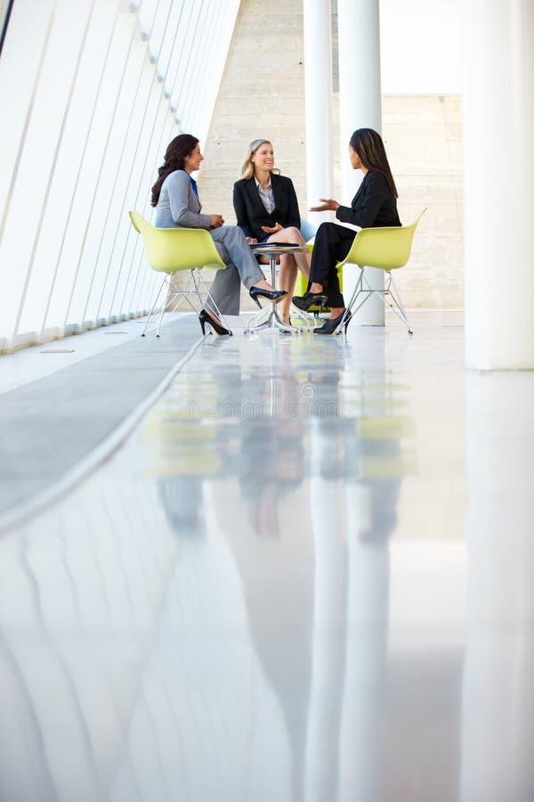 Trois femmes d'affaires se réunissant autour du Tableau dans le bureau moderne photo stock