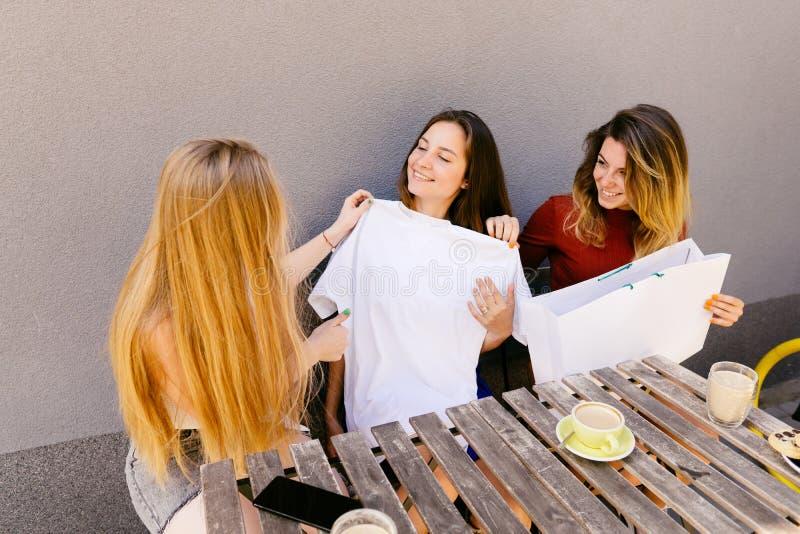 Trois femmes essayant le nouveau chemisier sur l'adaptation image stock