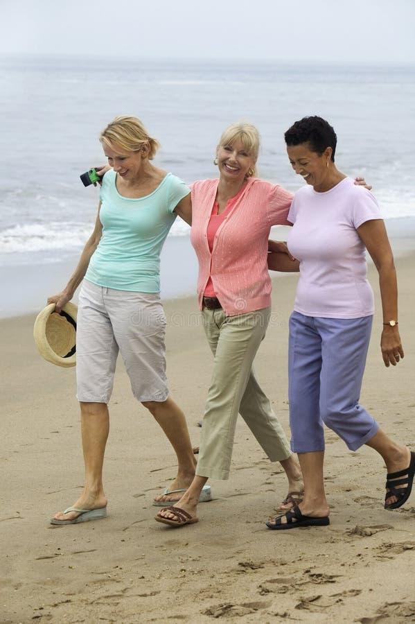 Trois femmes marchant sur la plage image stock