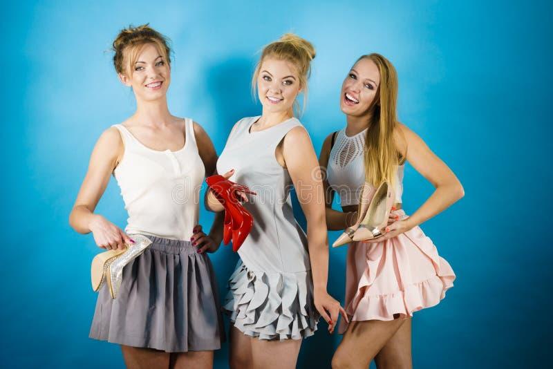 Trois femmes montrant des chaussures de talons hauts image stock