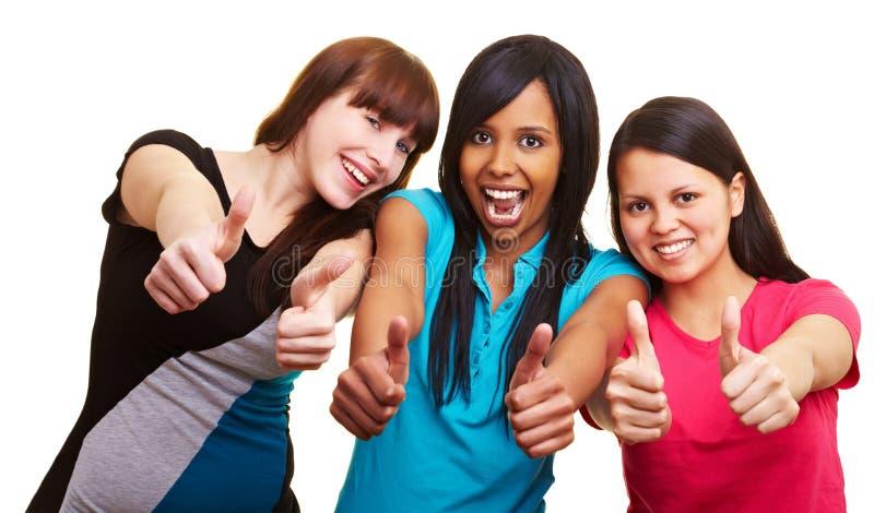 Trois femmes retenant leurs pouces vers le haut photos stock