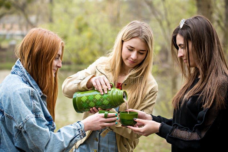 Trois femmes versent la boisson chaude de cacao photos stock