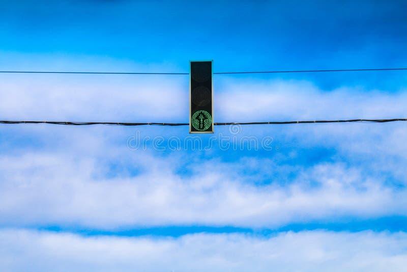 Trois feux de signalisation verts accrochent au-dessus de la route contre le ciel bleu Permettez le signal images libres de droits