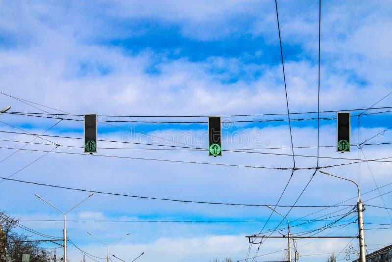 Trois feux de signalisation verts accrochent au-dessus de la route contre le ciel bleu Permettez le signal photos stock