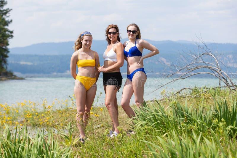 Trois filles atteignant le soleil un lac images libres de droits