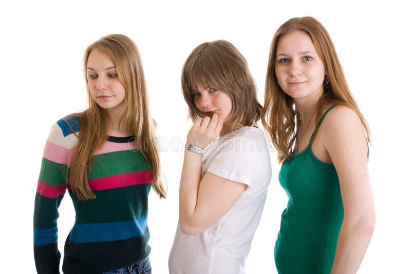 Trois filles attirantes d'isolement sur un blanc photographie stock