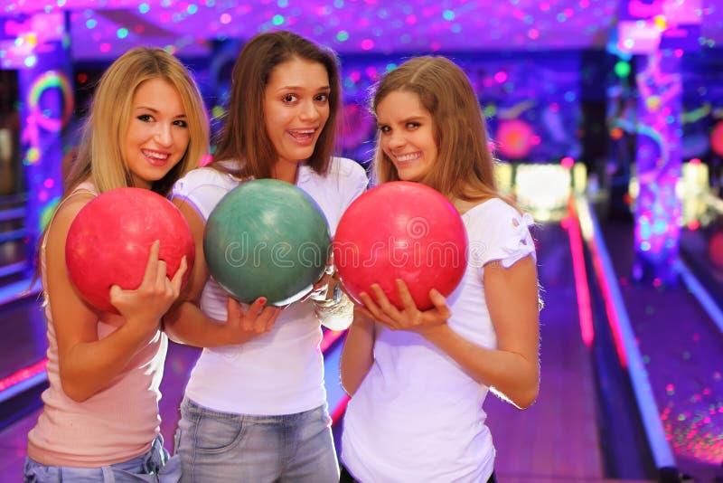 Trois filles avec des billes restent dans le club de bowling photos stock