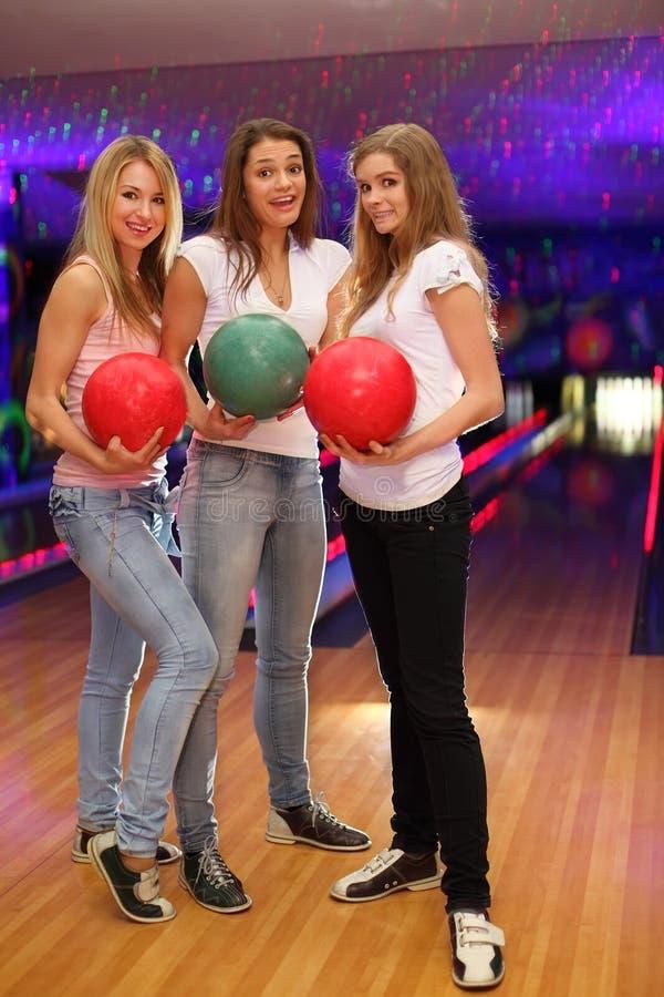 Trois filles avec des billes restent dans le club de bowling images stock