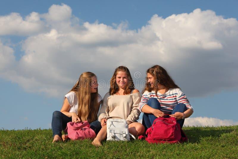 Trois filles avec la causerie de sacs et rient de l'herbe images stock
